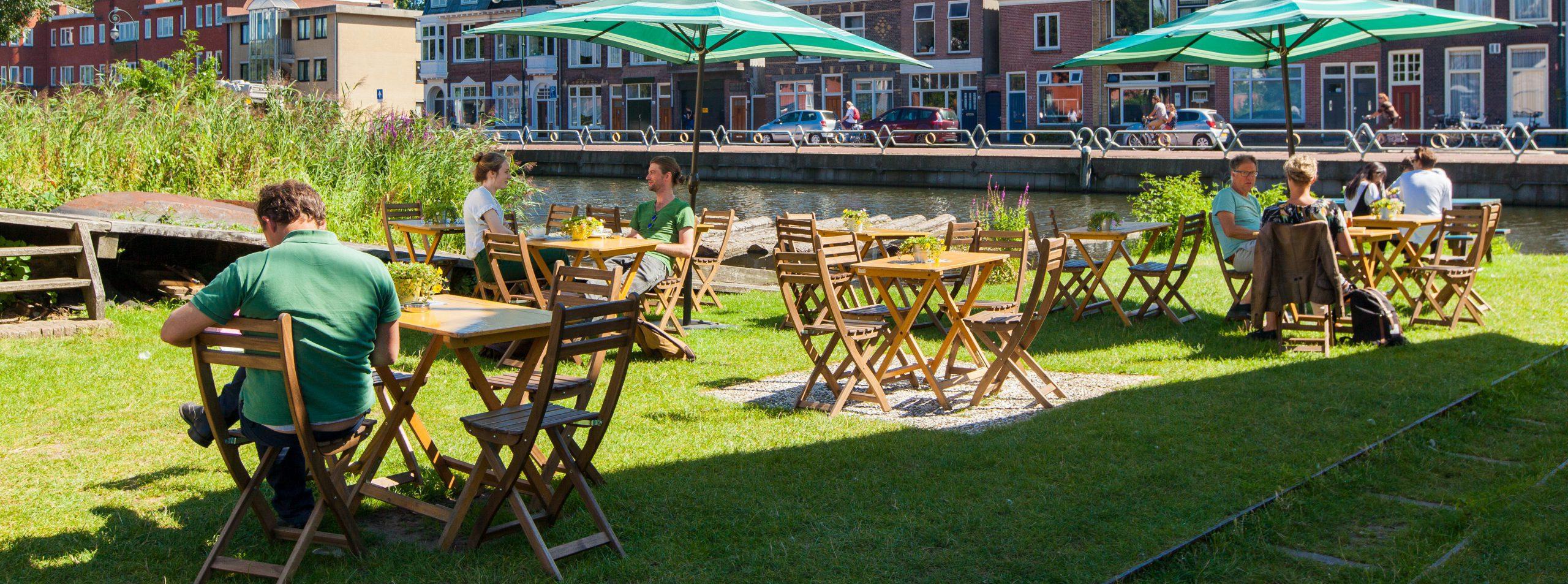 een terras op gras met een aantal tafeltjes waar mensen onder een parasol zitten in de zon. Op de achtergrond is water, huizen en verder op achtergrond is het stadskantoor van gemeente Utrecht te zien en nog twee bedrijfspanden.