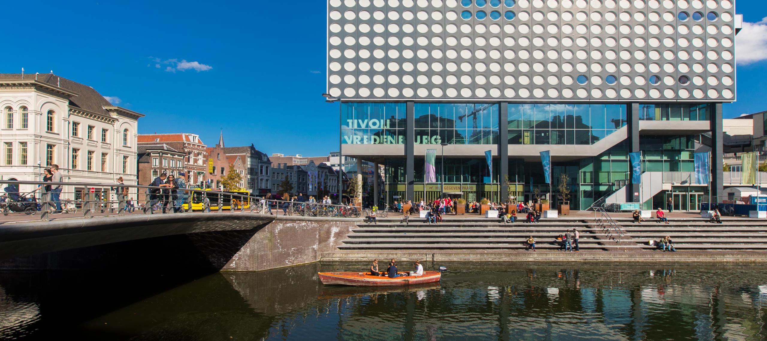 singel van Utrecht met een kano erin, op de achtergrond staat het gebouw van Tivoli Vredenburg en het centrum van Utrecht.