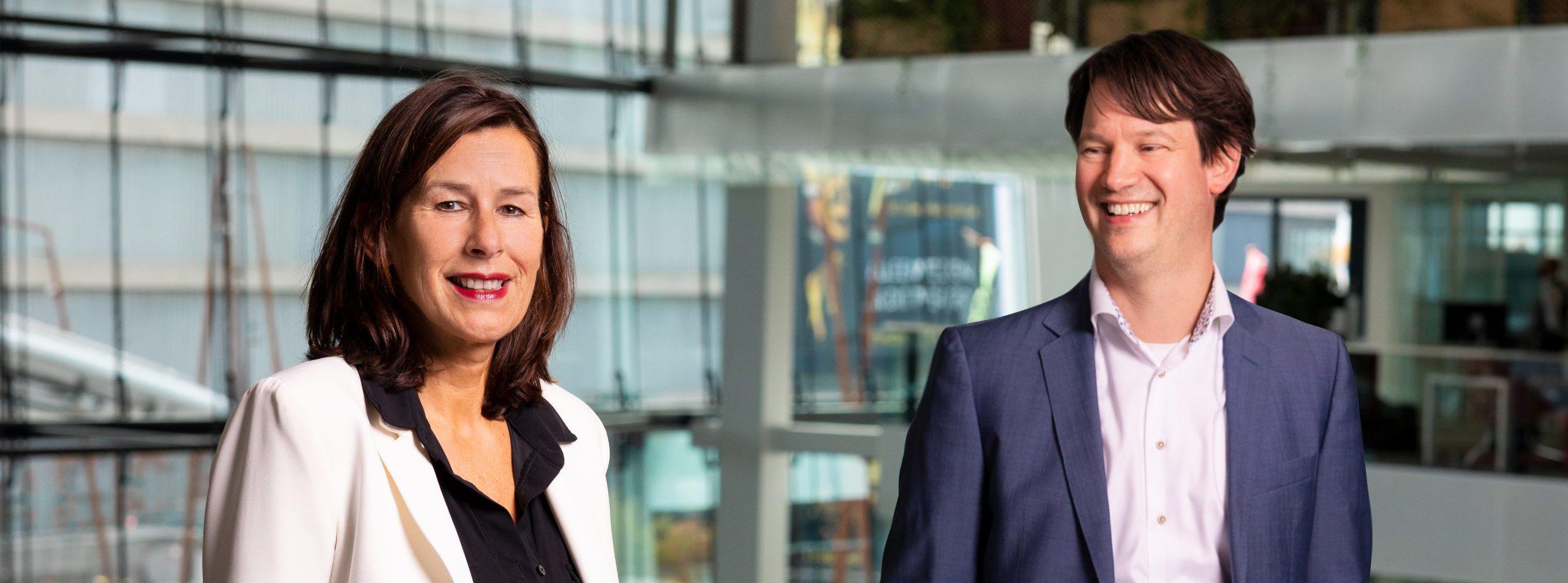 twee collega's (een vrouw en man) staan op een etage in het stadskantoor met uitzicht op de centrale hal van het stadskantoor.