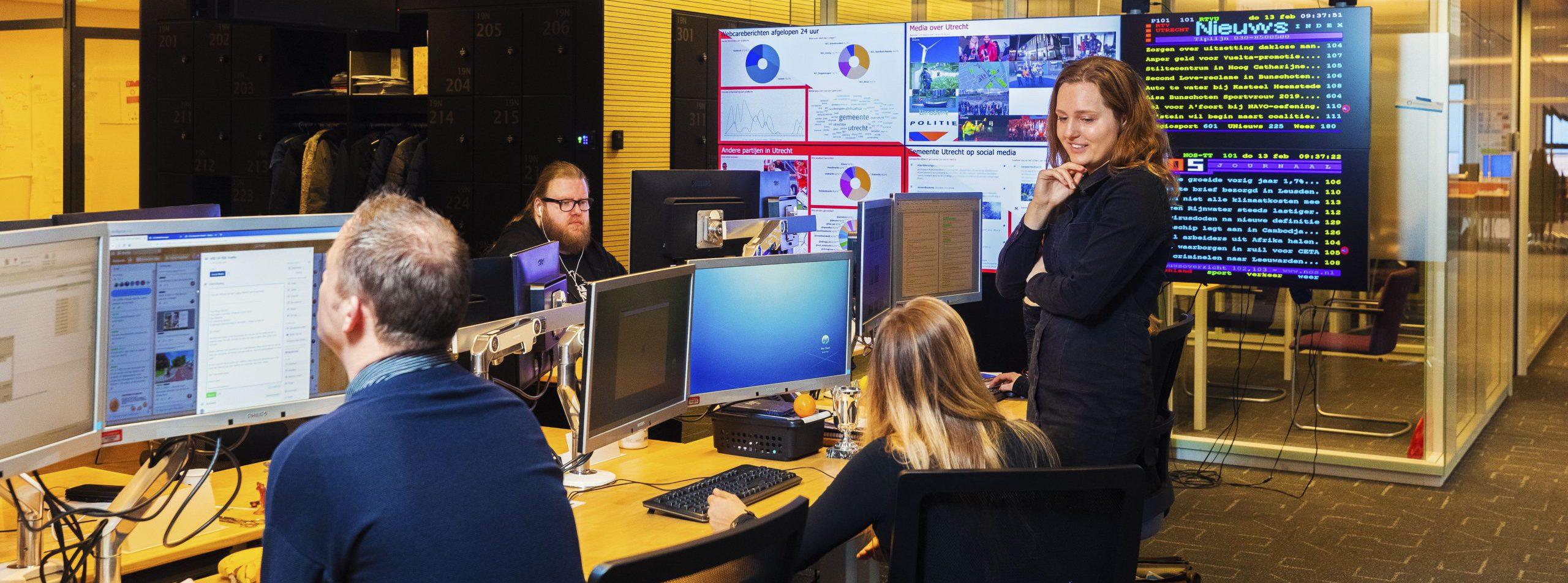 vier collega's die zitten en staan om een blok van zes bureaus bij communicatie van gemeente Utrecht. Op de achtergrond zijn verschillende beeldschermen waar al het nieuws wordt getoond en bijhegouden.