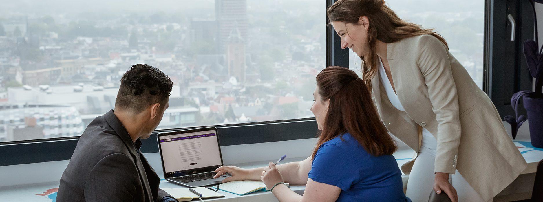 3 collega's die naar een laptop kijken, met op de achtergrond het uitzicht van Utrecht