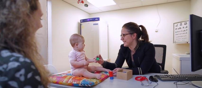 een jeugdarts zit aan haar bureau. Een moeder is met haar baby op bezoek. De arts bekijkt de baby.