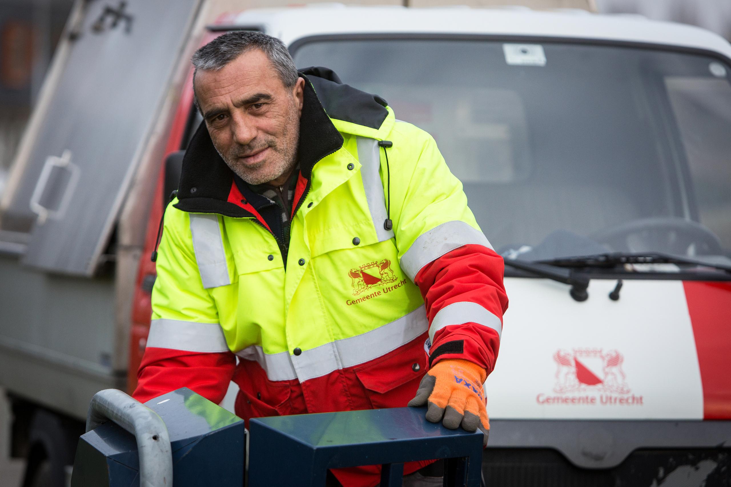 een vuilnisman leegt een prullenbak. Op de achtergrond staat een auto van de gemeente Utrecht.