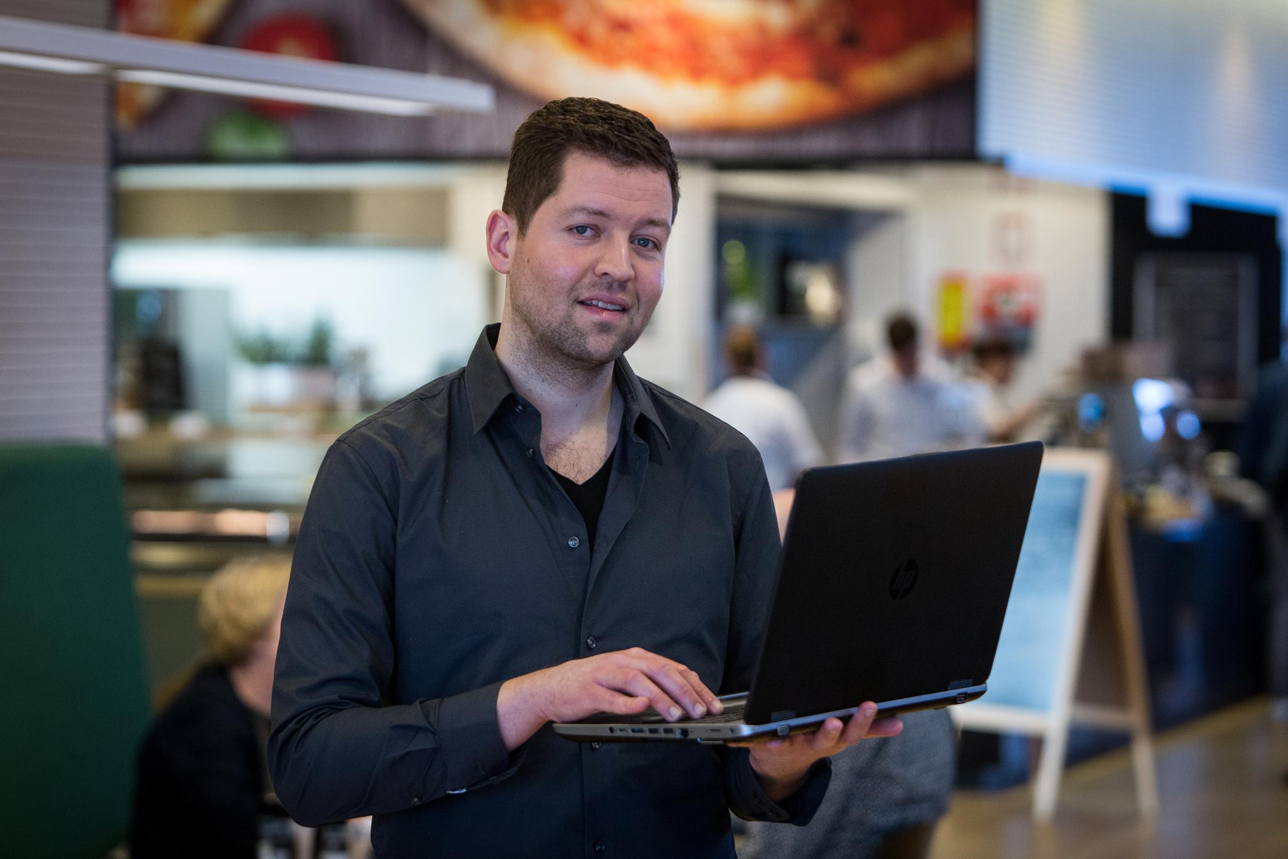 een mannelijke collega staat met zijn laptop zijn hand. Op de achtergrond is de koffiebar van het stadskantoor.