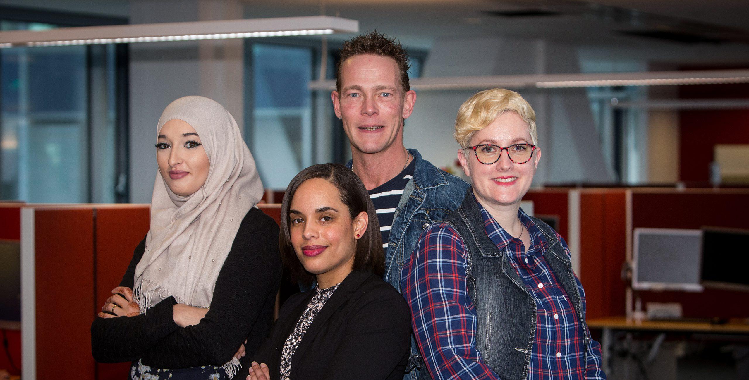 Een mannelijke en 3 vrouwelijke collega's van het Klant contact centrum met bureaus en beeldschermen op de achtergrond