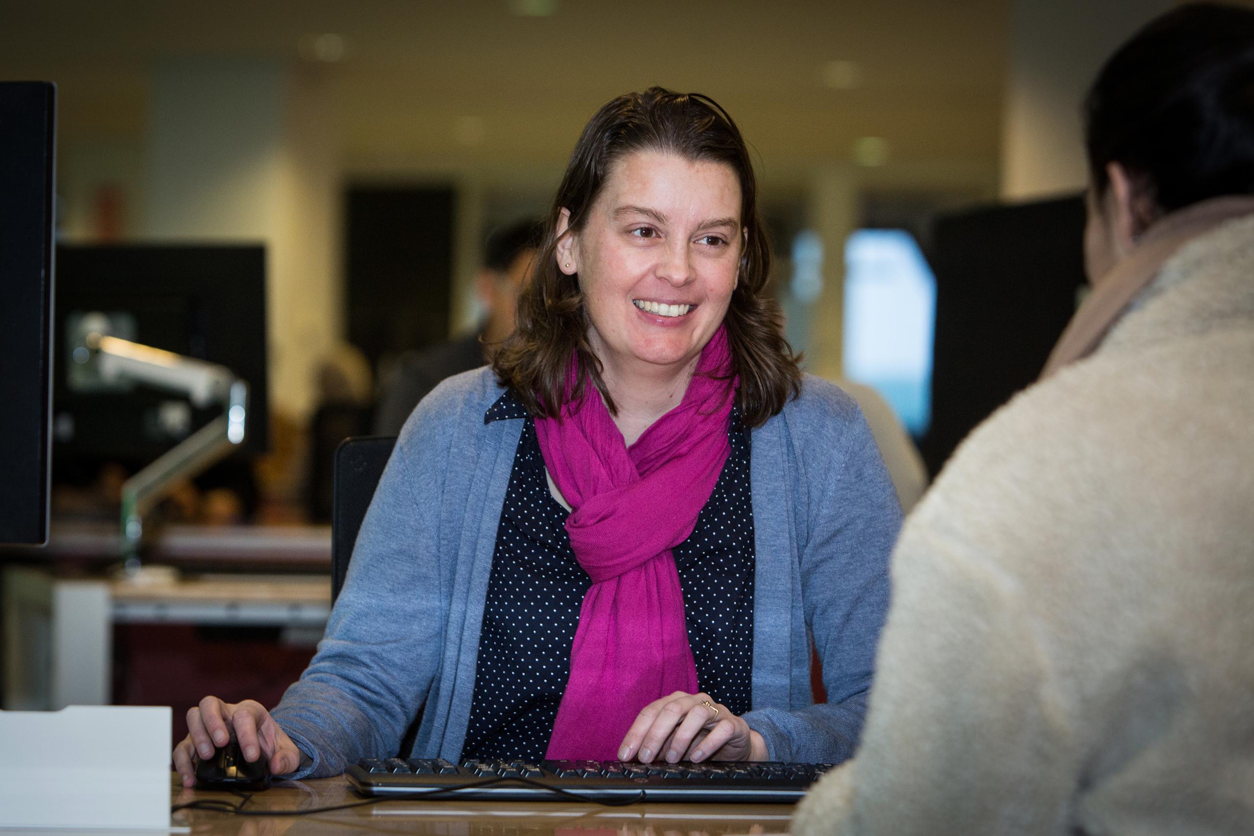 een vrouwelijke collega zit achter een balie en is in gesprek met een inwoner van Utrecht.